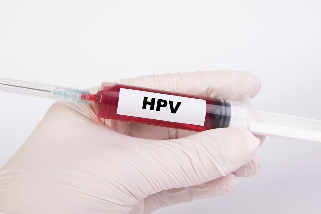 Spritze mit Injektionsnadel und dem Text HPV - ansteckender Virus