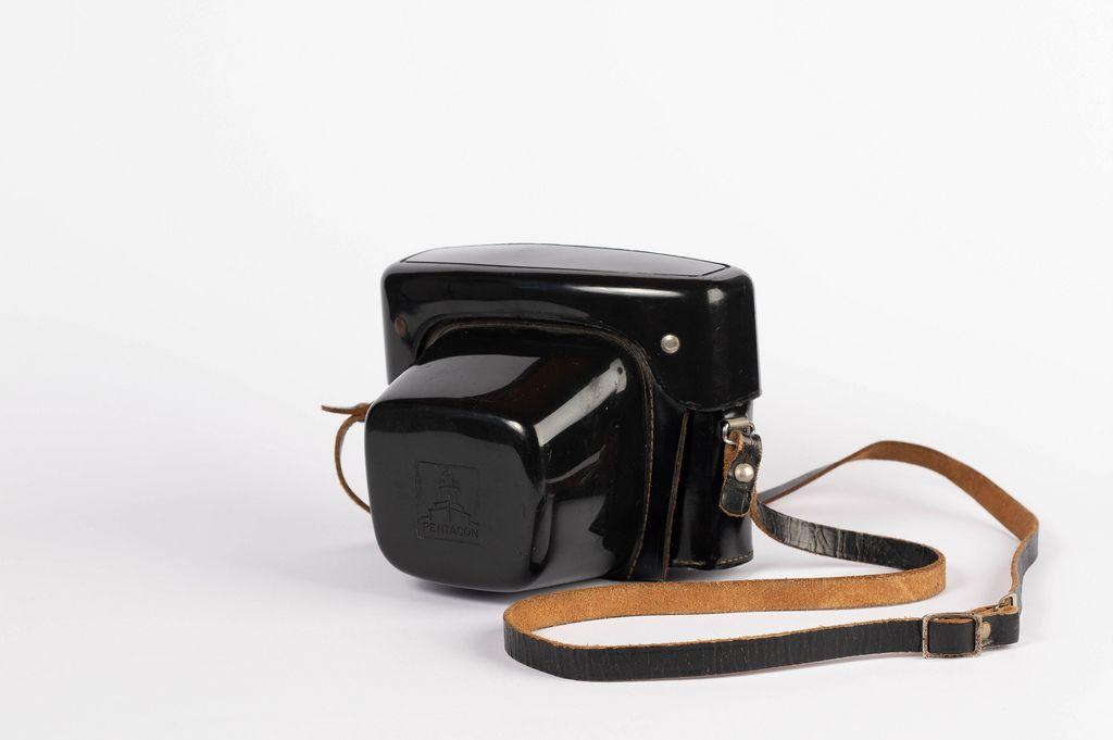 Stabile, schwarze Vintage-Kamerabox mit Lederriemen vor weißem Hintergrund