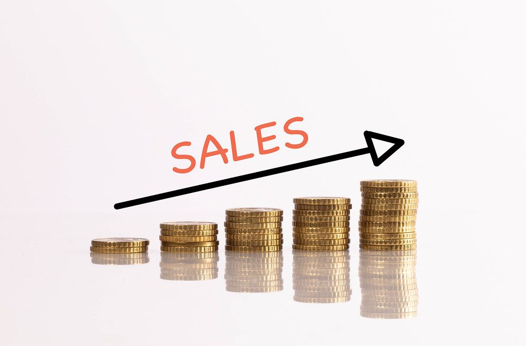 Stack of coins with arrow and sales text