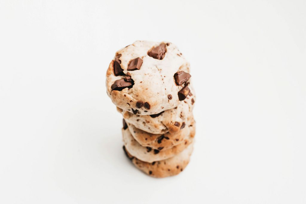 Stack of homemade chocolate chip cookies, vegan on white background