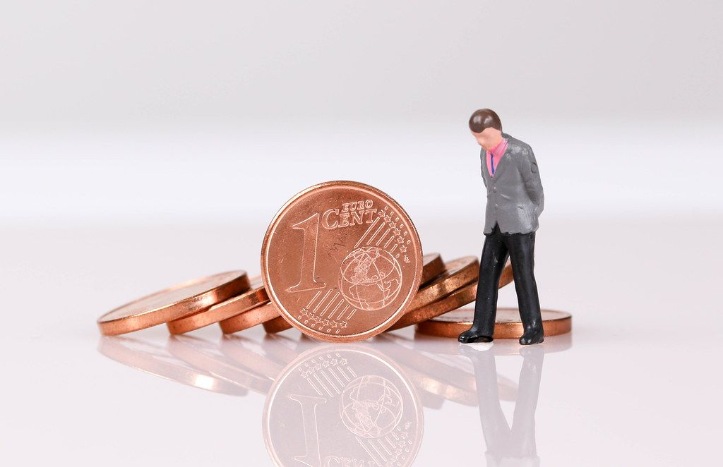 Stack of One Euro cent coins with businessman on white background