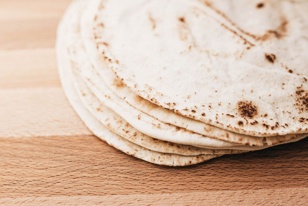 Stack of pita bread on wooden board
