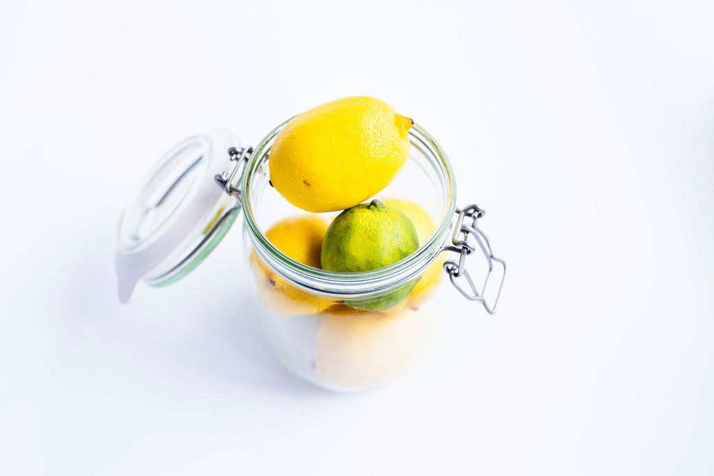 Stacked fresh lemons and lime in a metal jar on white background