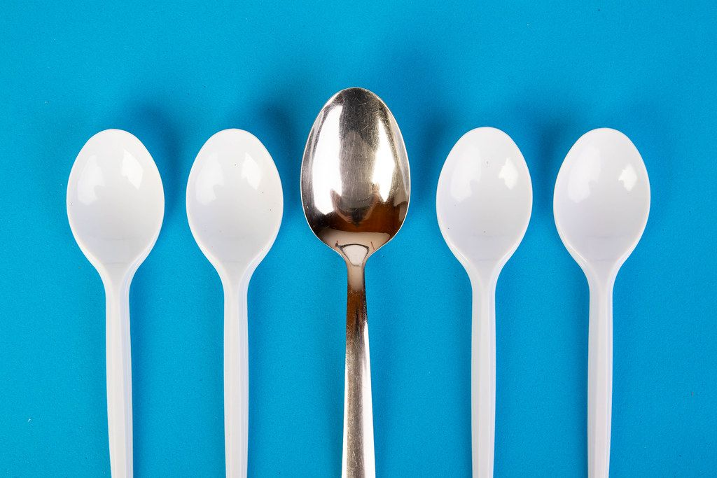 Stainless steel and plastic spoons on blue background