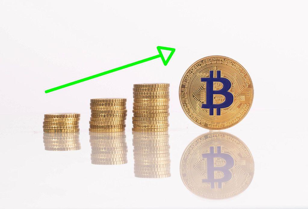 Stapel aus goldenen Münzen und Pfeil und goldener Bitcoinmünze