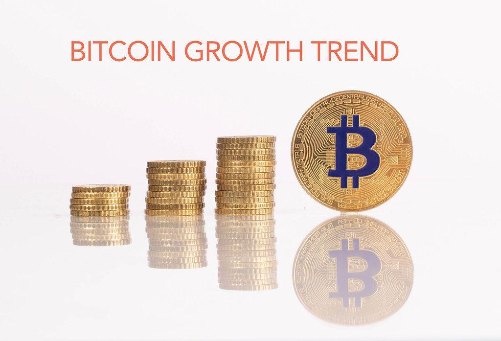 Stapel aus Goldmünzen mit goldener Bitcoinmünze und dem Text