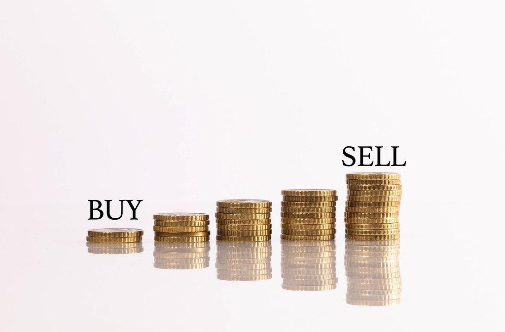 Stapel aus Münzen mit Kaufen und Verkaufen - Text