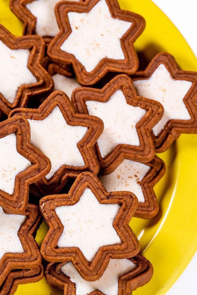 Sternförmige Weihnachtskekse mit Schokolade und weißer Füllung auf gelbem Teller