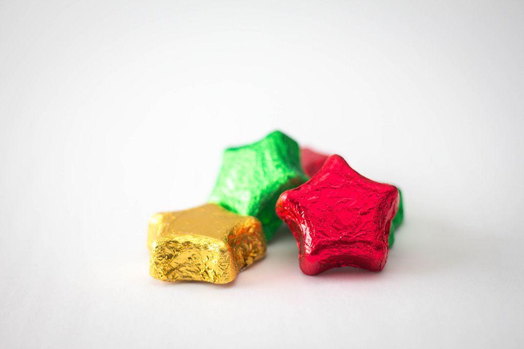 sternförmige Weihnachtsschokolade in gelber, roter und grüner Aluminiumverpackung vor weißem Hintergrund