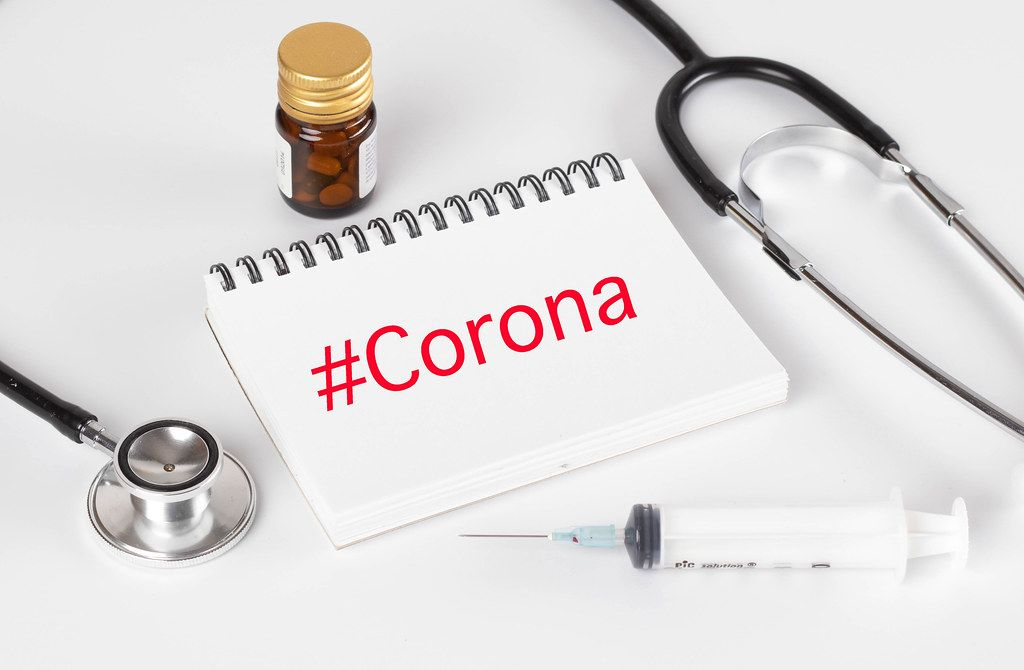 Stethoscope with notebook and syrige and #Corona text