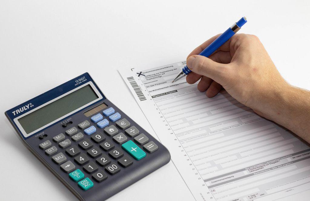 Steuererklärung wird ausgefüllt mit einem Taschenrechner auf einem Tisch