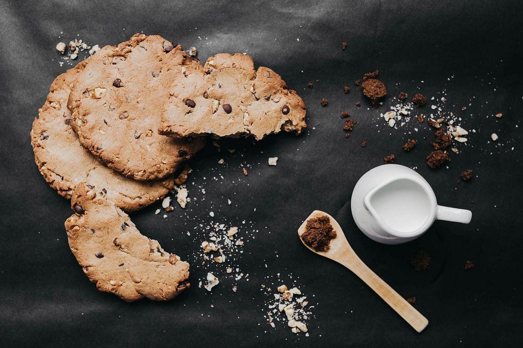 Stilisiertes Essen: Hausgemachte Schokostreusel-Kekse neben dunkelbraunen Rohrzucker und einem Kännchen voller Milch auf schwarzem Untergrund - Nahaufnahme in Draufsicht