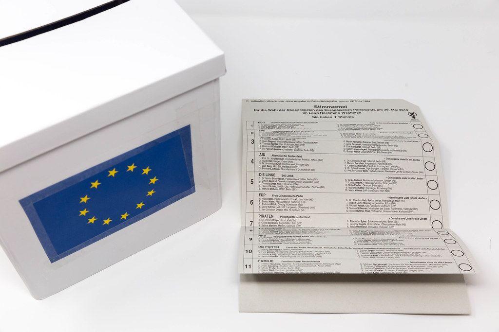 Stimmzettel der Briefwahlunterlagen für die Europawahl, mit einer Liste der teilnehmenden Parteien aus Deutschland, neben einer EU-Wahlurne