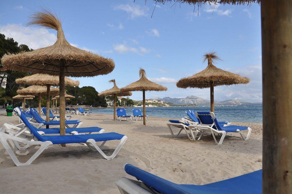 Strand mit Liegestühlen und Strohschirmen