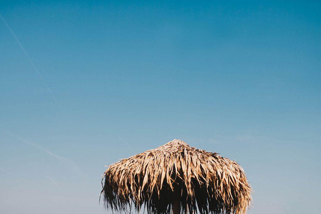 Straw umbrella on blue sky background. Summer.