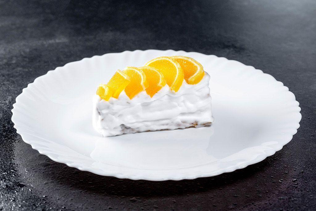 Stück Küchen mit Zitrusscheiben und weißer Sahne auf Teller, auf einem schwarzen Tisch