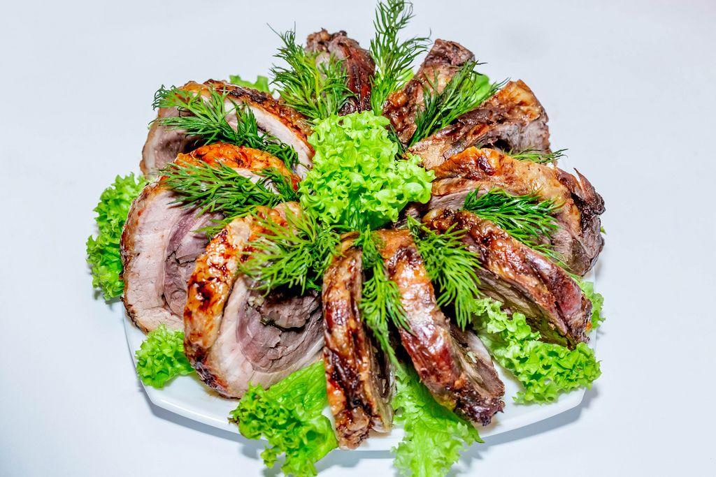 Stücke von Schweinefleisch-Roulade schön angerichtet mit Kräutern und Salaten vor weißem Hintergrund