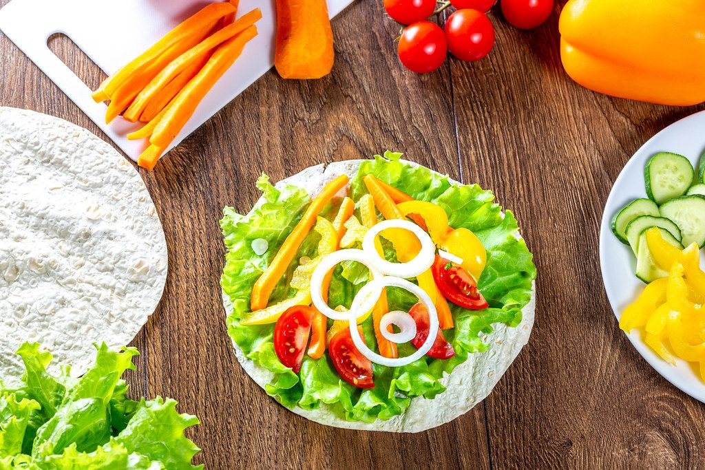 Summer ripe vegetables and pita on wooden background