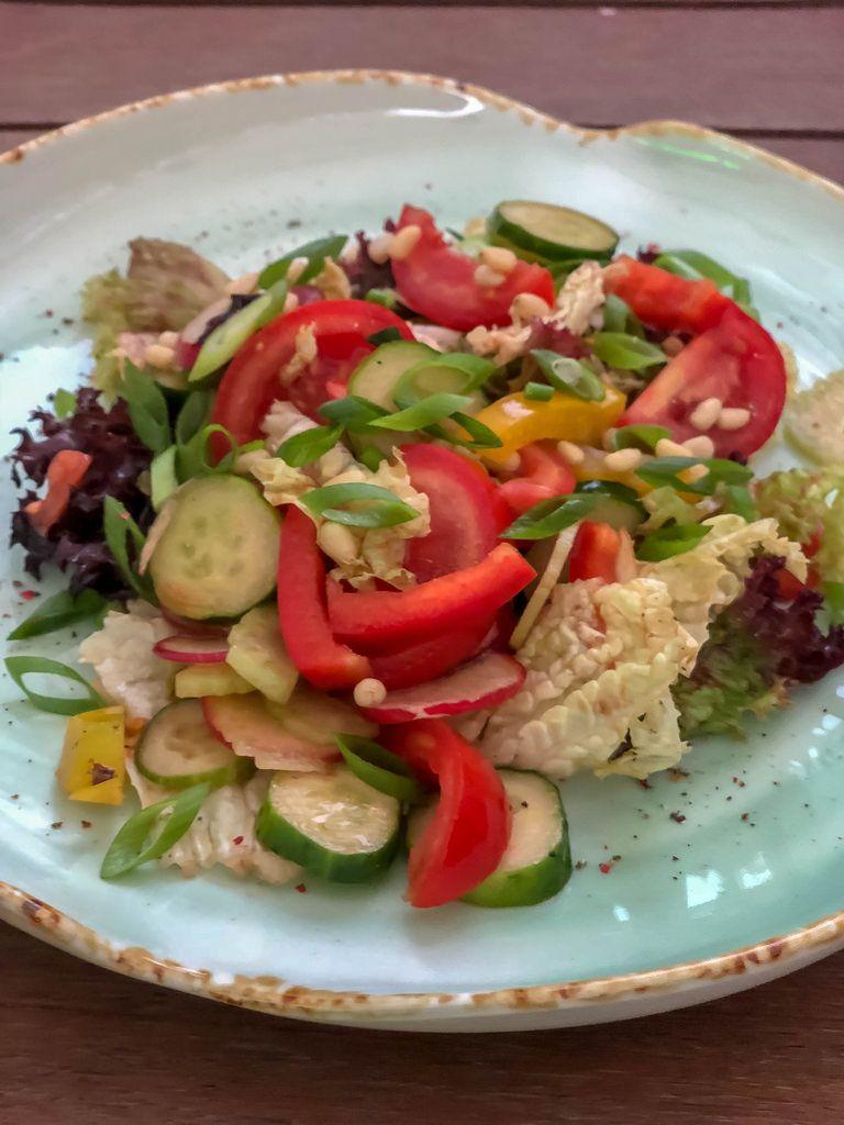 Summer salad at Avocado Cafe: tomatoes, cucumbers, sweet pepper, celery lettuce leaves, pine nuts, balsamic vinegar, olive oil, lemon juice