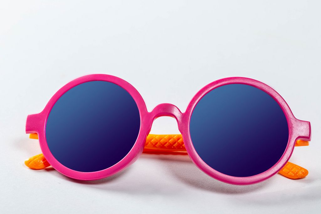 Sunglasses pink-orange colors on white. Kid's party concept