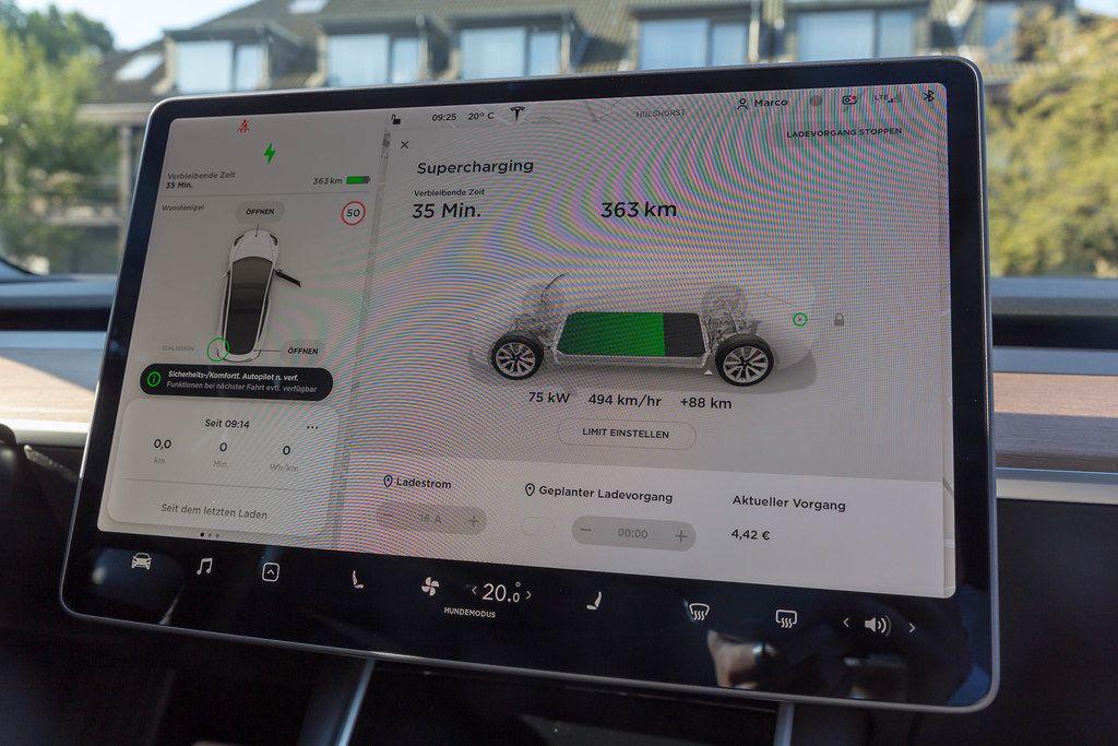 Supercharging-Batterieanzeige auf dem Display, während der Elektroauto-Ladung an einer Tesla Supercharger Ladestation