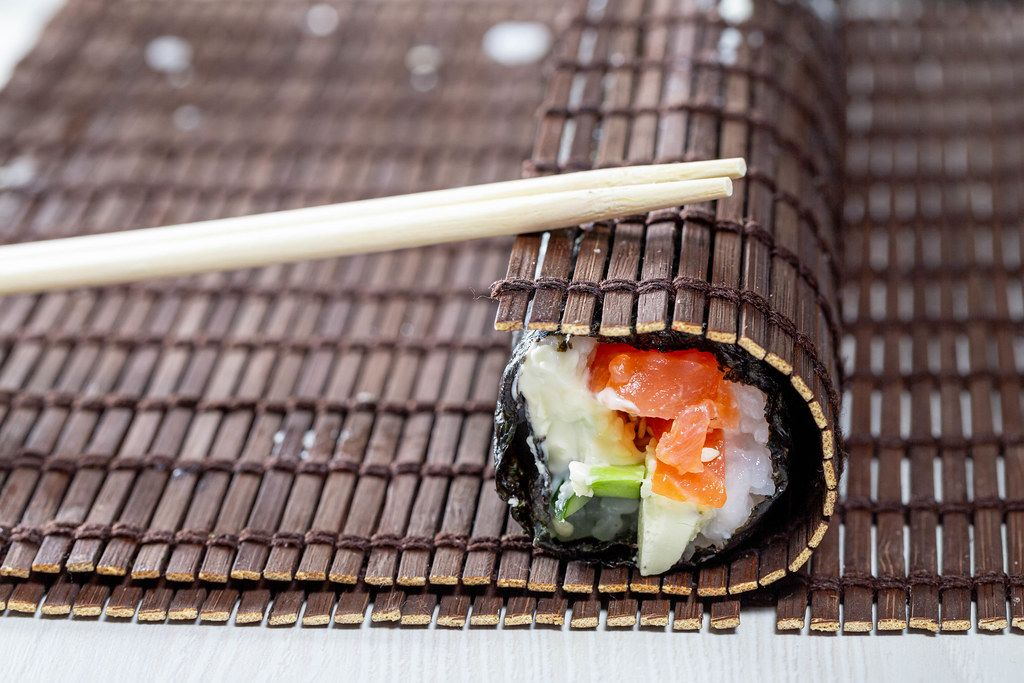 Sushi roll wrapped in bamboo Mat with chopsticks (Flip 2019)