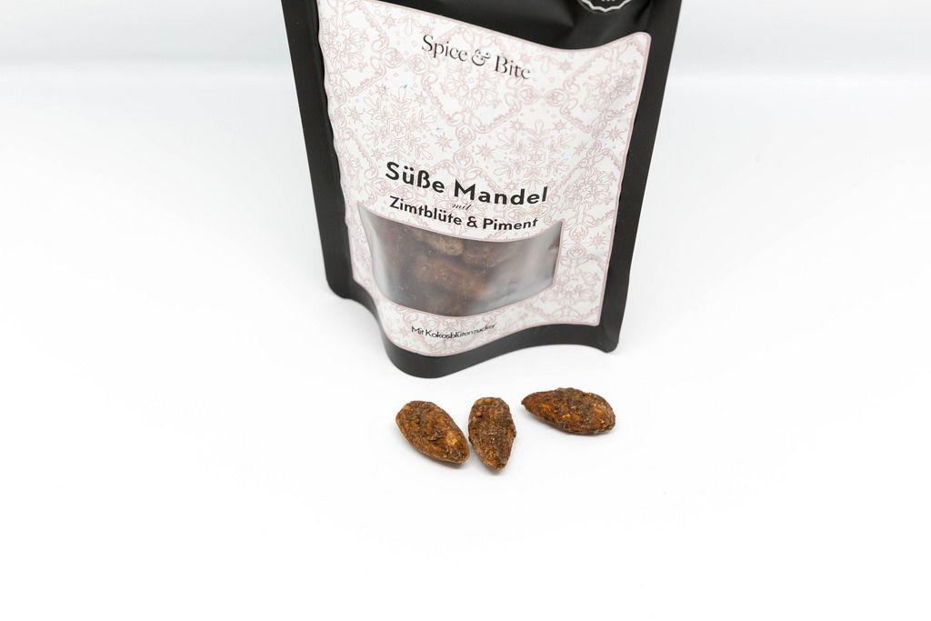 Süße Mandeln mit Zimtblüte und Piment vor weißem Hintergrund