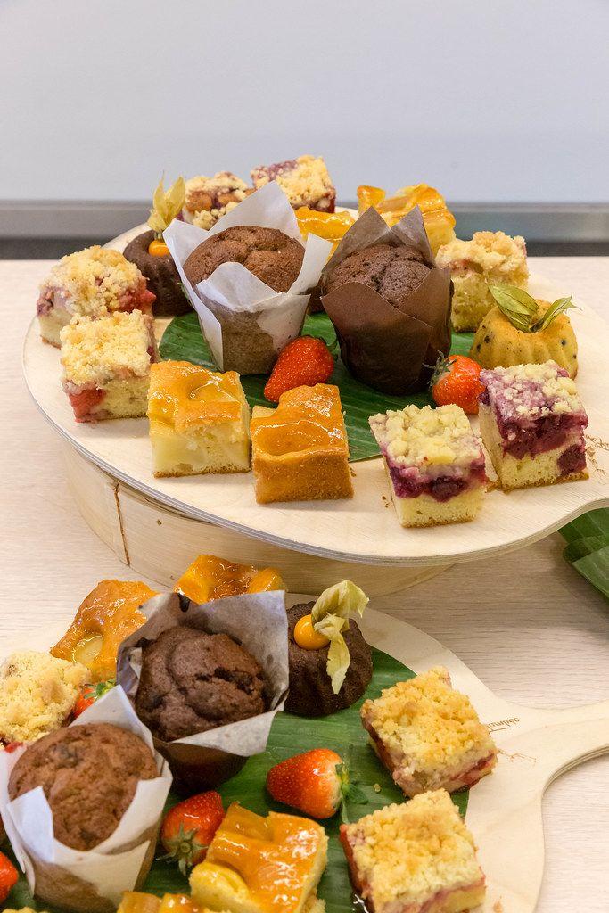Süße Nachspeisen angerichtet auf runden Holzbrettchen mit Kuchen, Früchten und Muffins, beim Mittagessen im AXA-Gebäude während des Barcamps OMWest19 in Köln