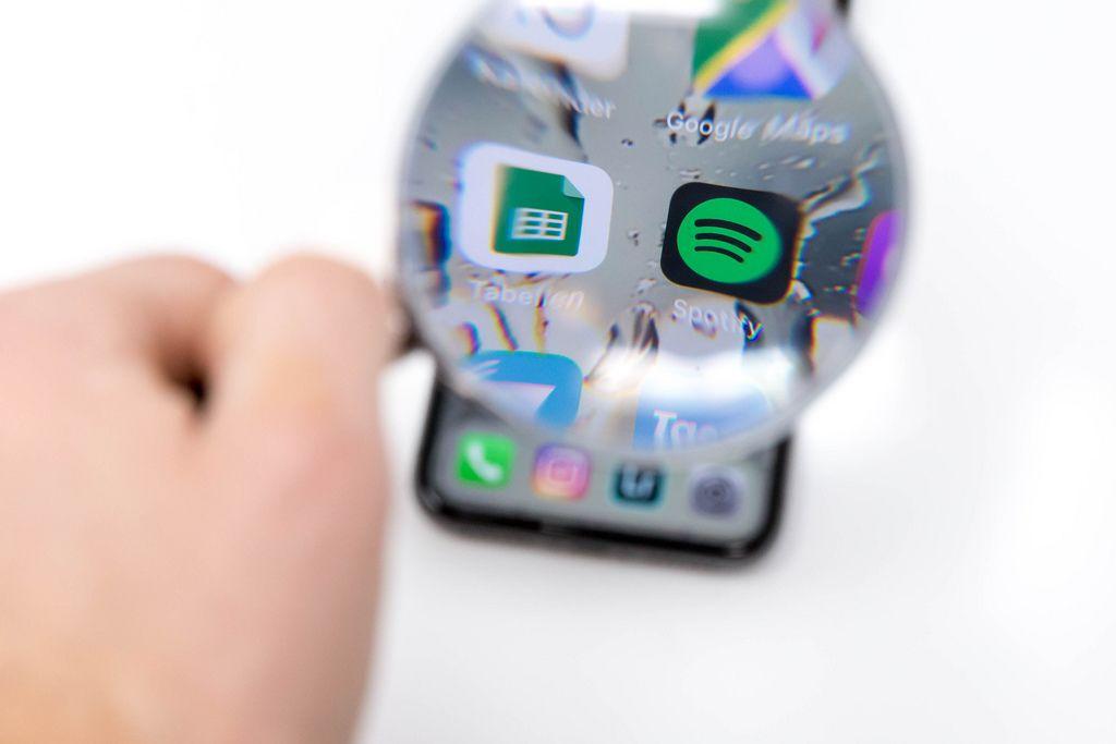 Tabellen App und Spotify App Icon auf schwarzem Smartphone durch Lupe betrachtet vor weißem Hintergrund