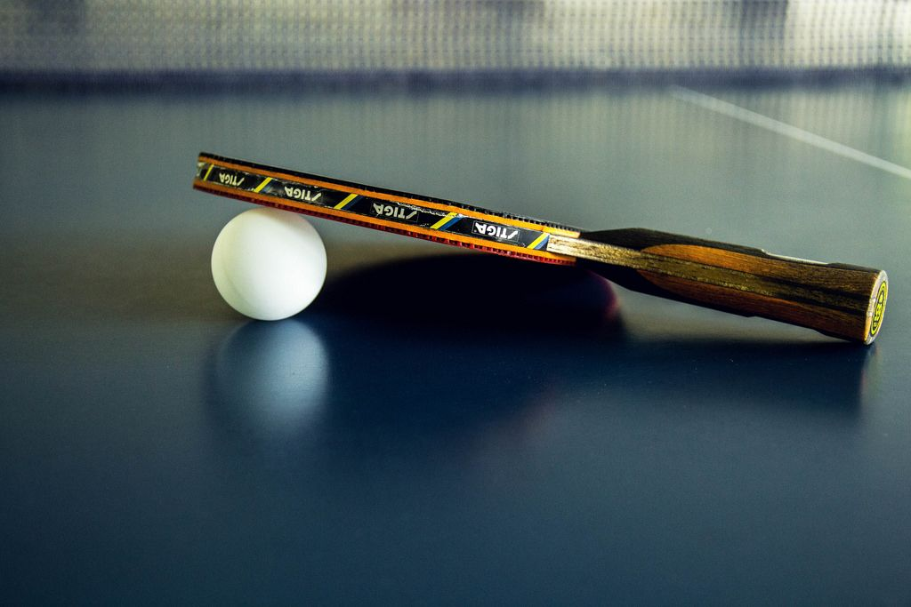 Table Tennis Paddle and Ball Resting on the Table
