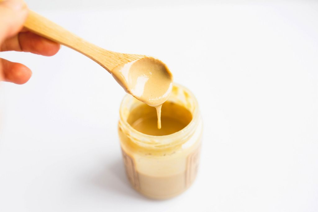 Tahini spread in a jar with wooden spoon on white background