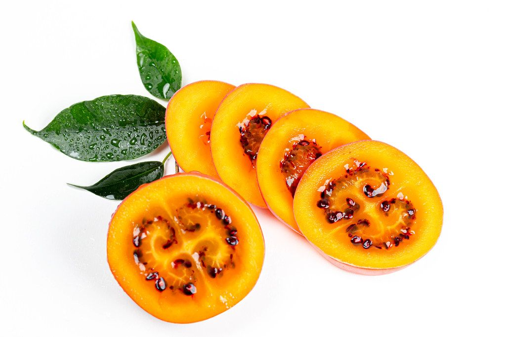 Tamarillo sliced and half on white background with leaves