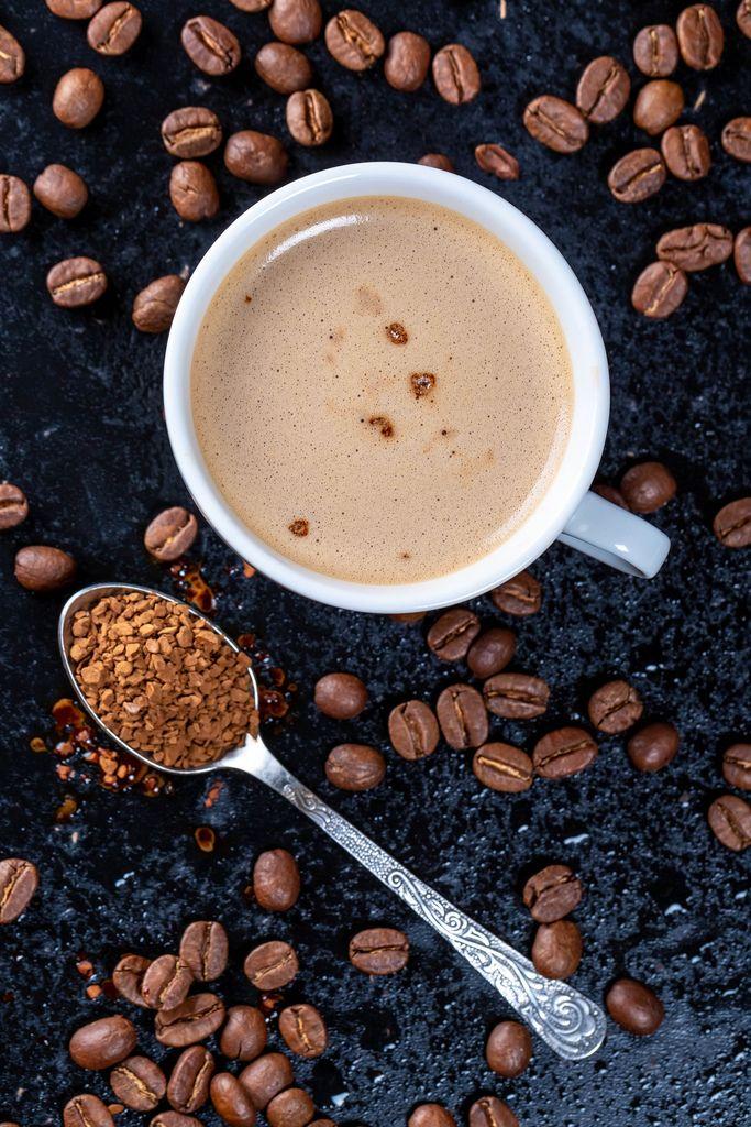Tasse mit gemahlenem Kaffee, geraspeltem Kaffee auf einem Löffel und Kaffeebohnen auf schwarzem Untergrund aus der Vogelperspektive