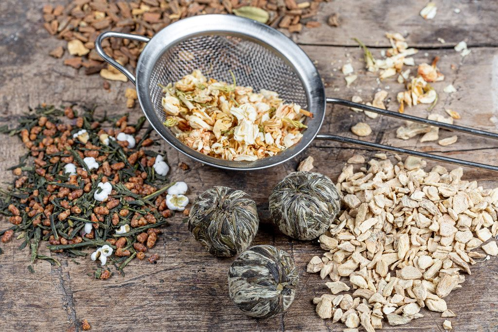 Tea background with different varieties of teas and a sieve on a wooden background