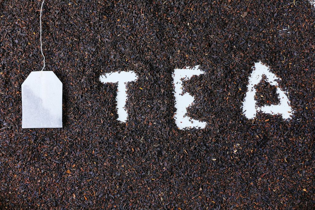 Tea bag and letters on dry tea background