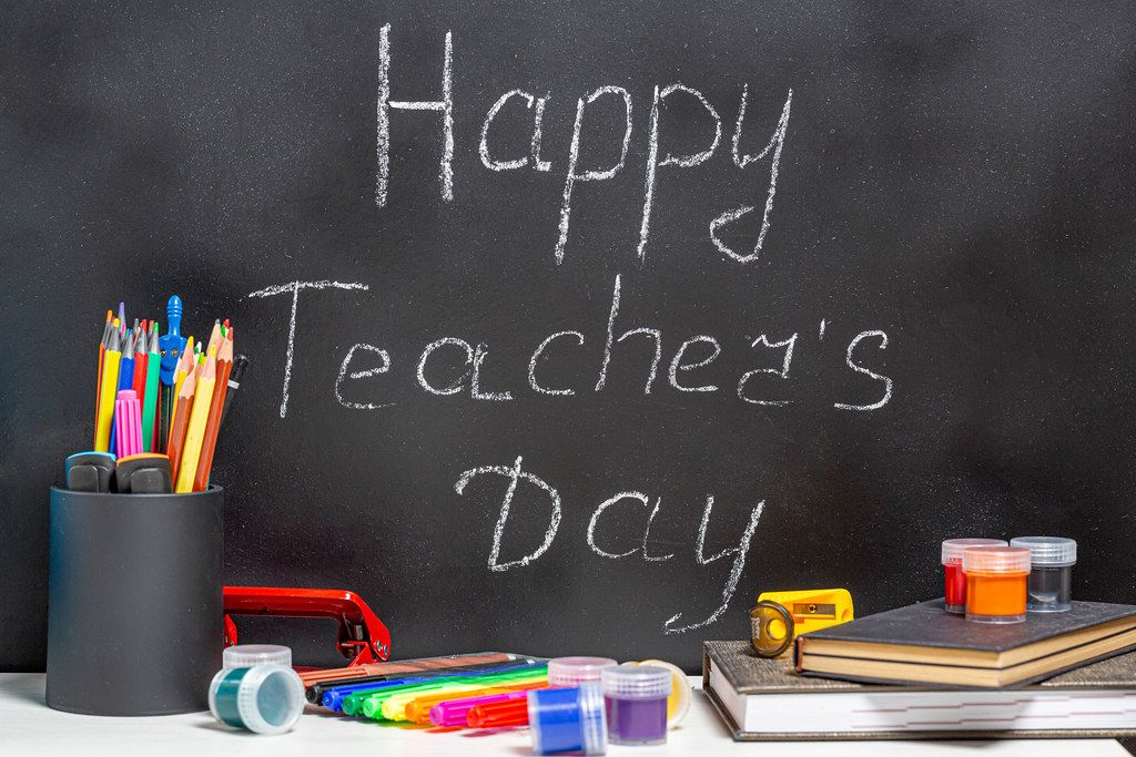 Teacher books and a stand with pencils on the table, on the background of a blackboard with chalk. The concept of the teacher's day