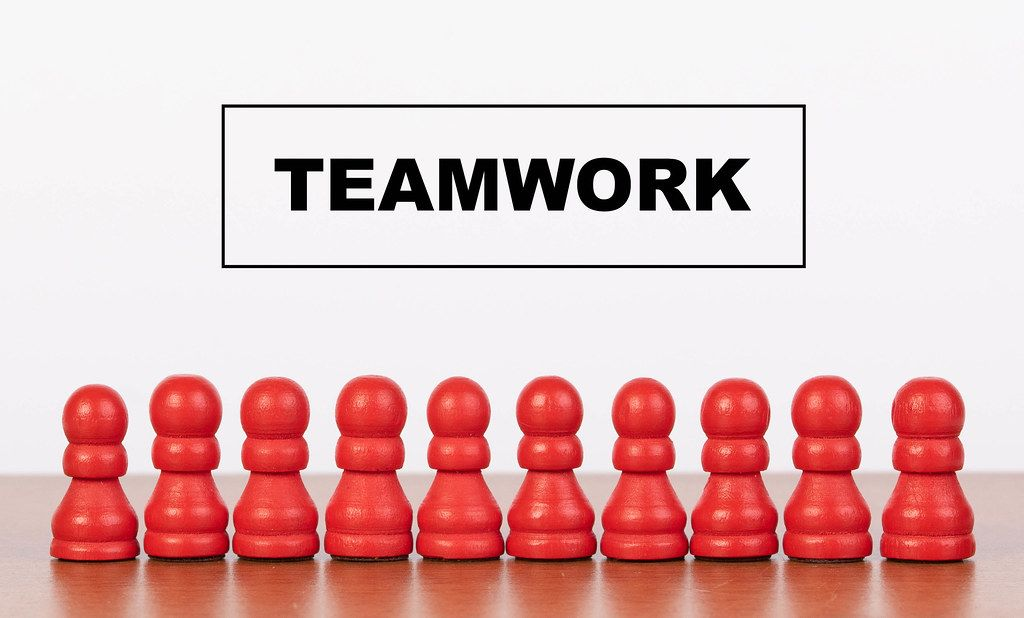 Teamwork concept with pawn figurines on table