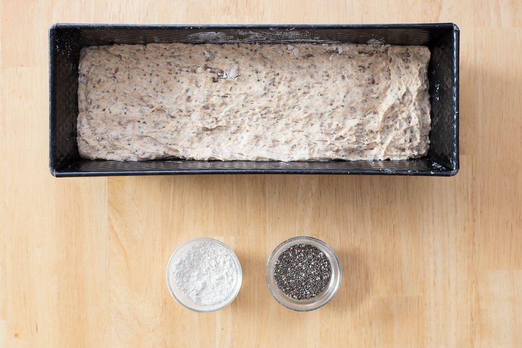 Teig für Chia-Brot in der Form sowie Mehl und Chia-Samen in kleinen Glasschüsseln