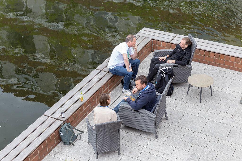 Teilnehmer des Barcamps OMWest zum Thema Onlinemarketing entspannen auf Rattanstühlen auf einer Veranda am See des AXA-Gebäudes in Köln