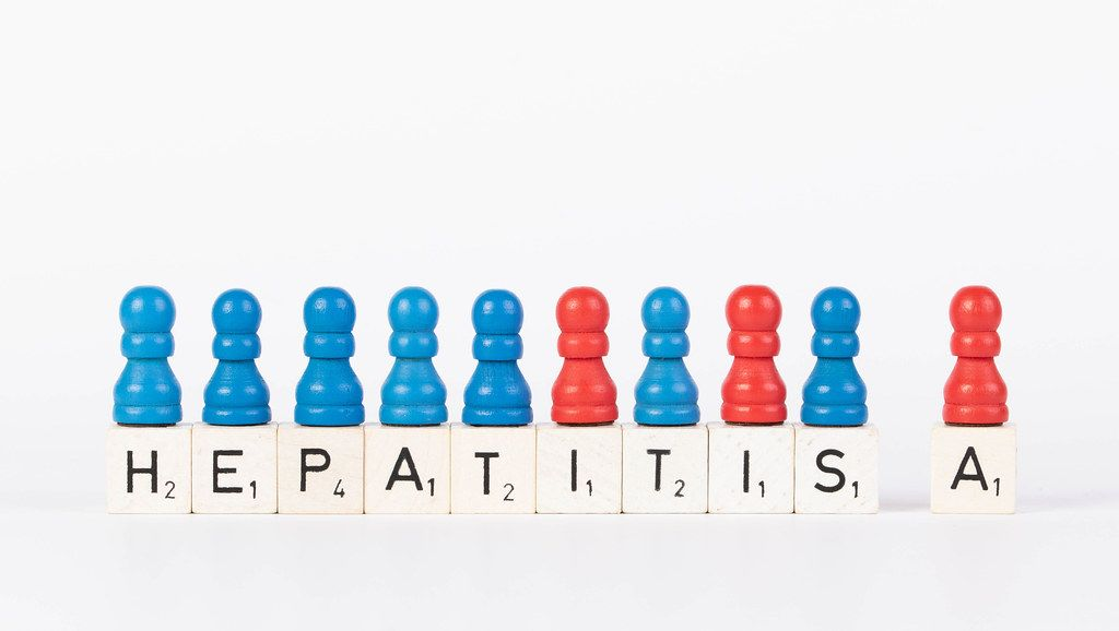 Text Hepatitis A written on wooden blocks with pawns in various colors on white background