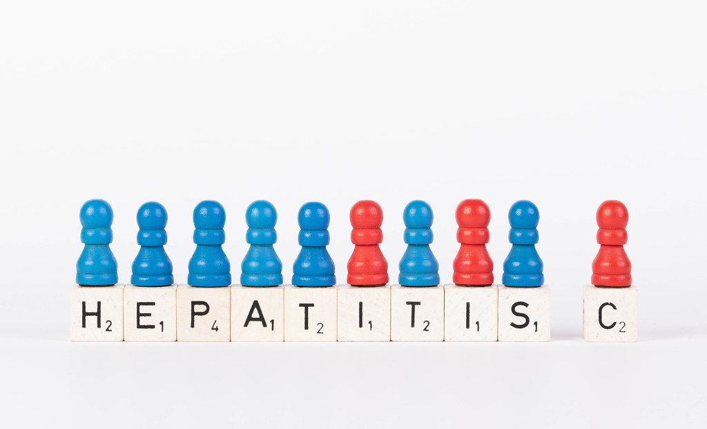 Text Hepatitis C written on wooden blocks with pawns in various colors on white background