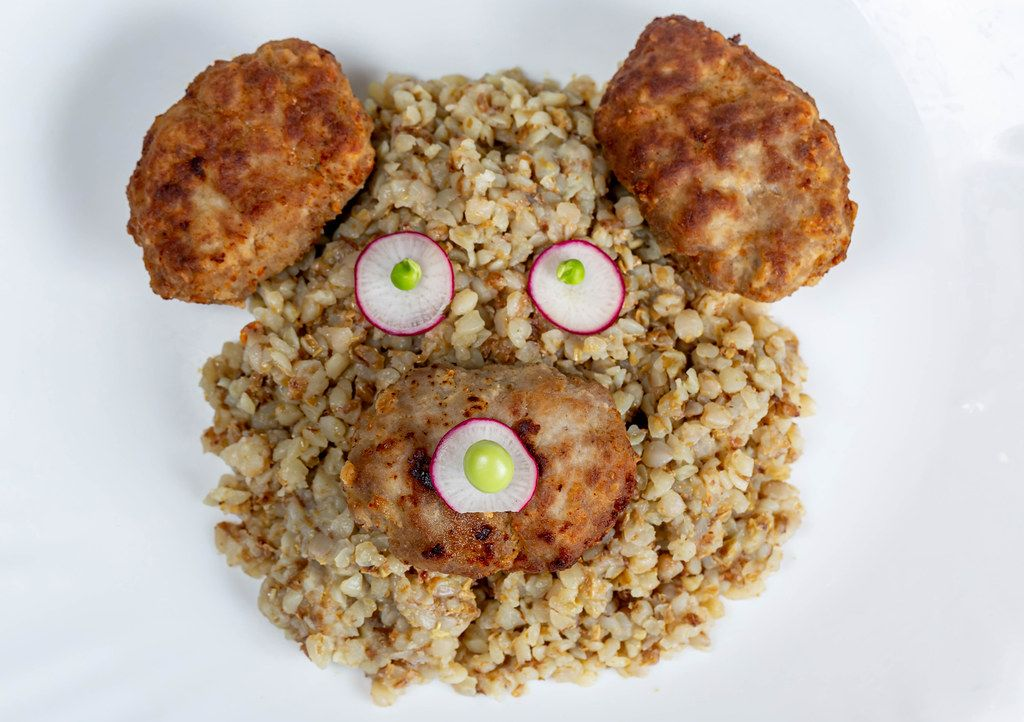 The concept of a children's lunch. The face of a bear made of buckwheat porridge, cutlets and radishes