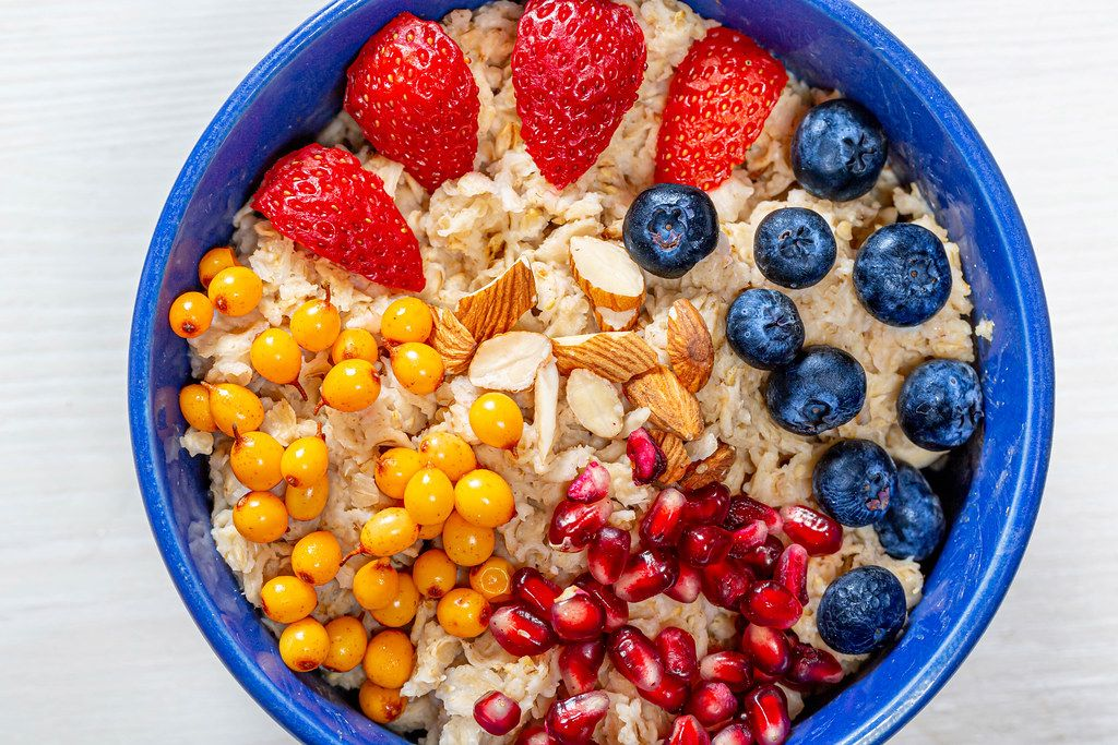The concept of a healthy Breakfast-oatmeal with fruit and almonds