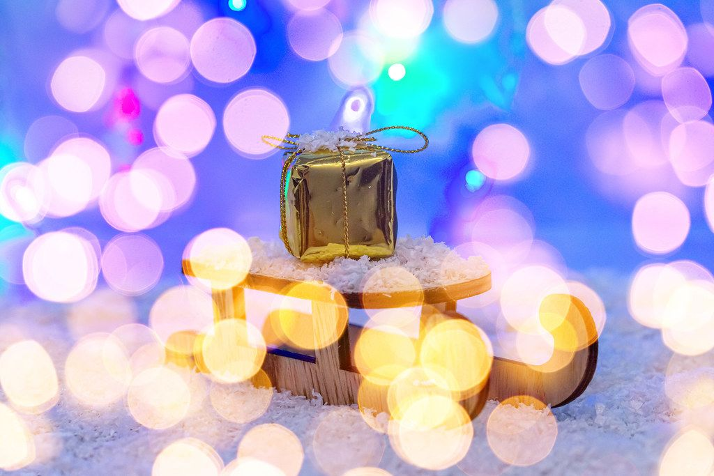 The concept of preparation for winter holidays. Sleigh with gift on snow with bokeh (Flip 2019)
