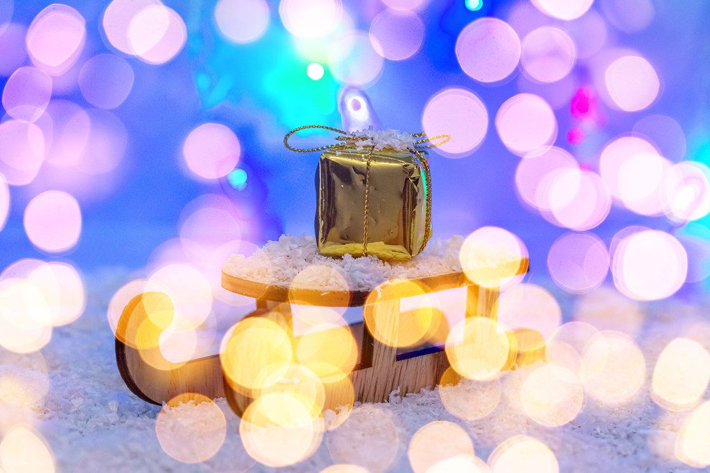The concept of preparation for winter holidays. Sleigh with gift on snow with bokeh