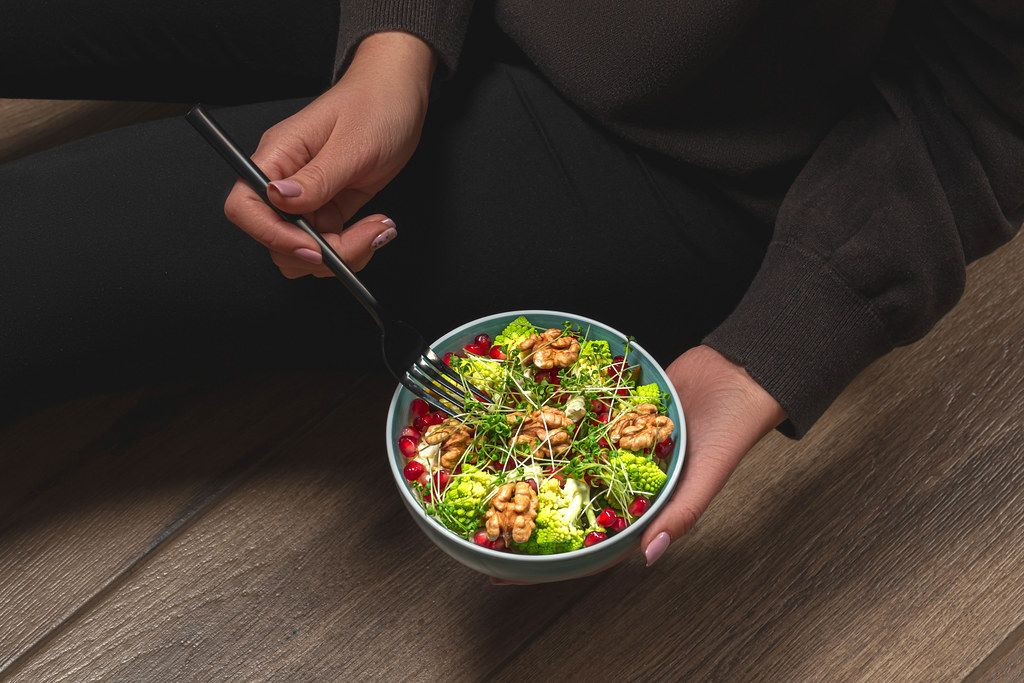 The concept of proper nutrition. A woman with a diet salad in her hands
