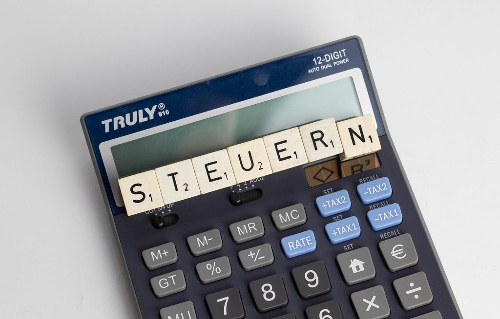 The German word 'Steuern' shot from above with digital calculator lying underneath