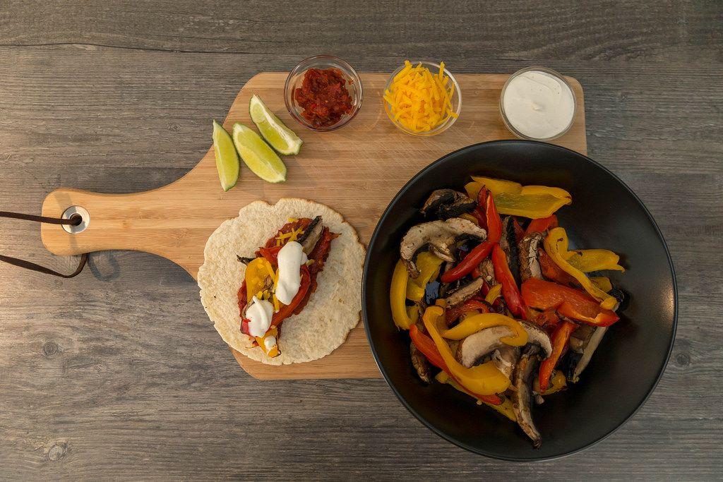 The ingredients for the hello fresh receipt: vegan fajitas with peppers, mushrooms, hot sauce and lime-cream on a cutting board - top view