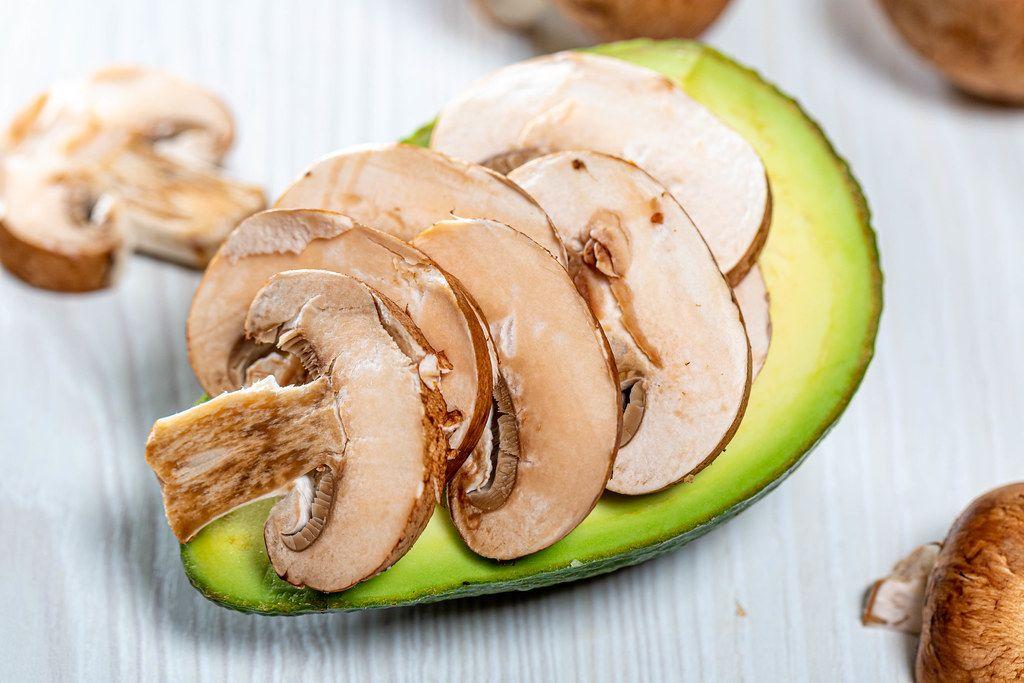 The mushroom pieces fresh avocado - preparing to bake