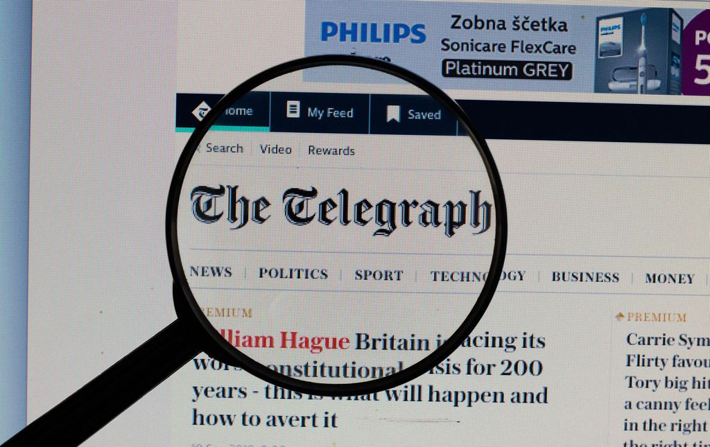 The Telegraph Logo am PC-Monitor, durch eine Lupe fotografiert
